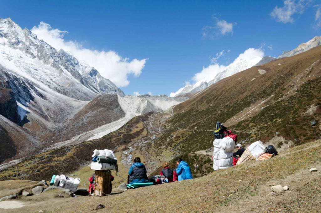Porters rest as they are approaching Dharmasala. Last point before the Larke Pass. They carry heavy loads, mainly food.